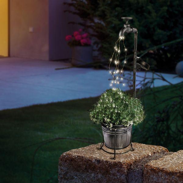 Wasserhahn mit Lichterbündel und Pflanzgefäß